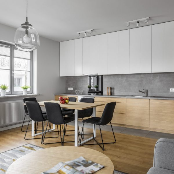 Contemporary kitchen with modern furniture and big table with black chairs